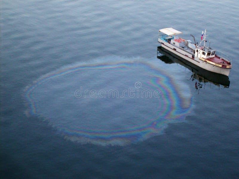 Inquinamento delle acque da una persona in barca immagini stock libere da diritti