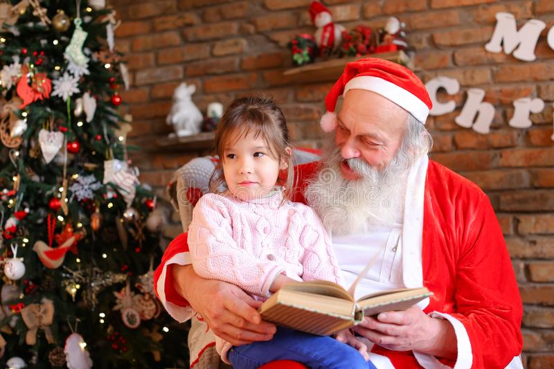 Santa Claus sits on armchair and reads book with fairy tales stock photo