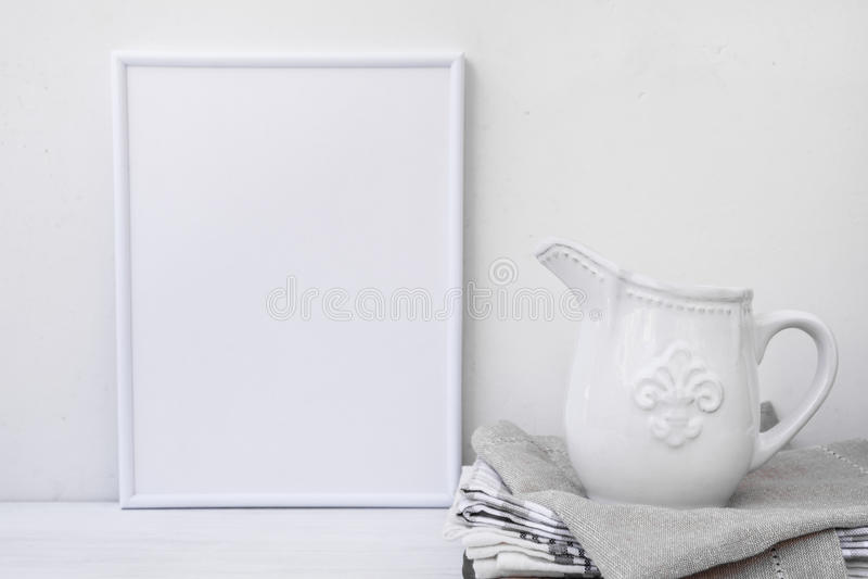 Inrama modellen, den vita tappningkannan på bunten av linnehanddukar, den minimalist rengöring utformade bilden royaltyfri bild