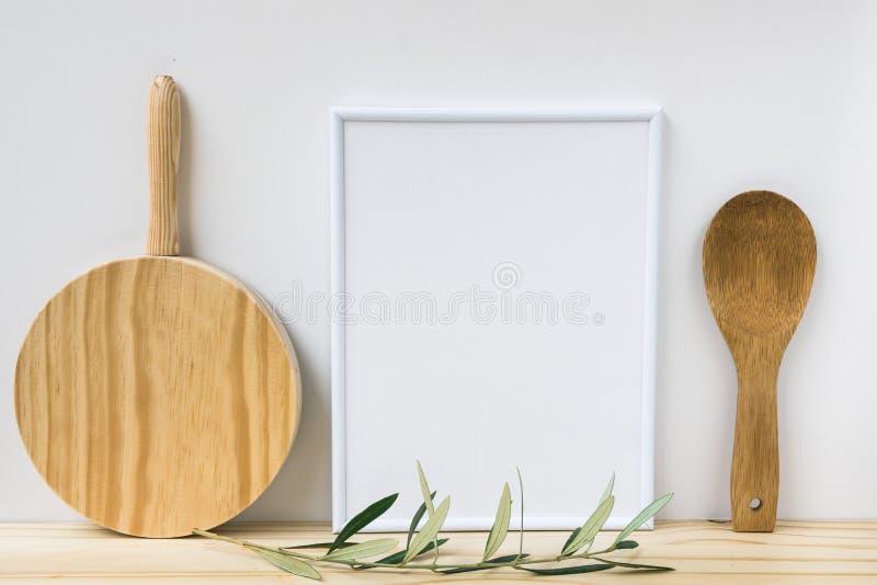 Inrama modellen, den wood skärbrädan, skeden, olivträdfilial på vit bakgrund, utformad bild arkivbilder