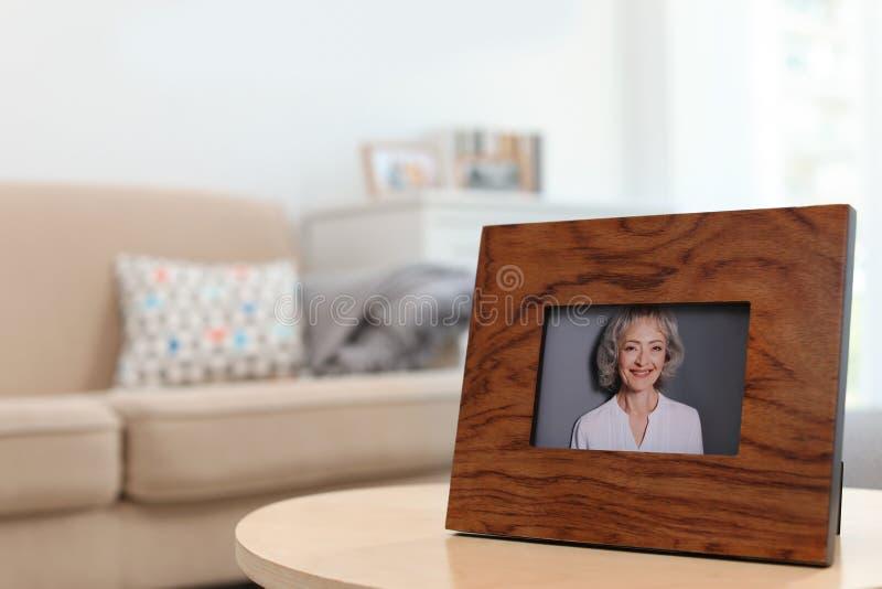 Inramad stående av den höga kvinnan på tabellen inomhus royaltyfri bild