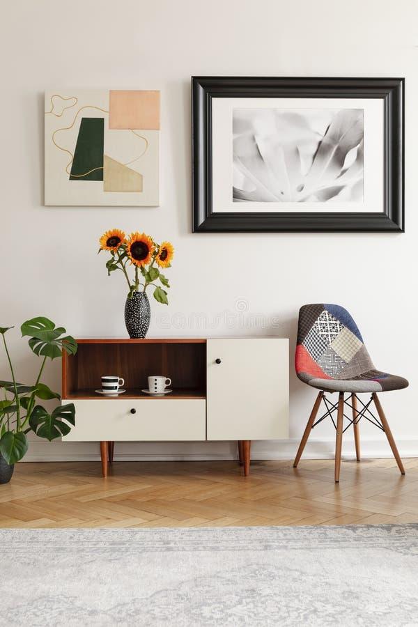 Inramat foto och abstrakt konst ovanför solrosor på ett elegant kabinett och en patchworkstol i den vita vardagsruminre royaltyfria bilder