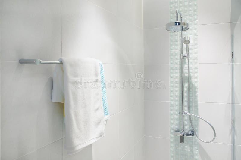 Inre av badrummet med det moderna duschhuvudet och vithandduken royaltyfria bilder