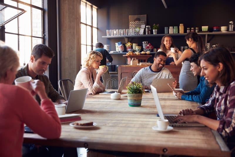 Inre av coffee shop med kunder som använder Digital apparater arkivfoton