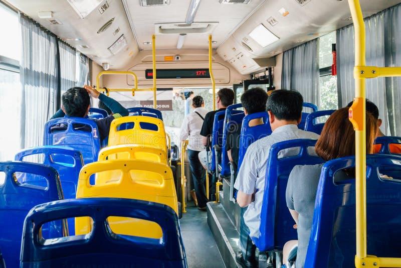 Inre av den moderna kinesiska stadsbussen med folk arkivfoto