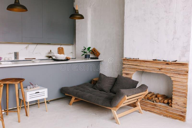 Inre av den moderna vindkök-studion i lägenheten Rum möblemang, soffa nära träspisen arkivfoto