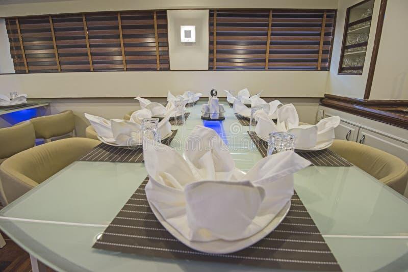 Inre av den stora salongen som äter middag område av lyxmotoryachten royaltyfria bilder