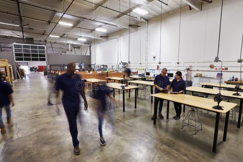Inre av den upptagna fabriken med personalen på arbetsbänkar arkivbild