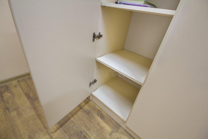 Inre av den vita plast- kabinett- eller beklädagarderoben med många tomma hyllor med öppna dörrar Möblemangdesign och installatio arkivbild