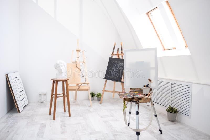 Inre av den vita studion av konstnären, idérik person Staffli, borstar, murbrukhuvud och diagram Loft höga tak arkivfoto