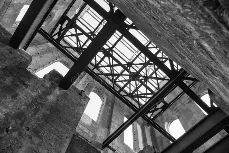 Inre av en förstörd gammal industribyggnad som ser upp på takbalkar arkivbilder