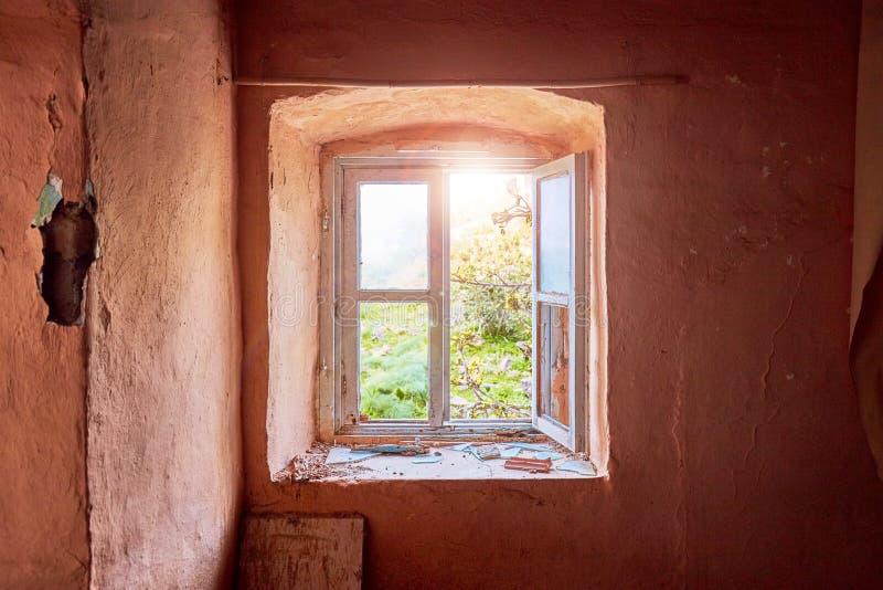 Inre av en förstörd gammal stuga med ett ljust - rosa vägg och bruten träen fönsterram som beskådar ett lantligt grönt ängfält fotografering för bildbyråer