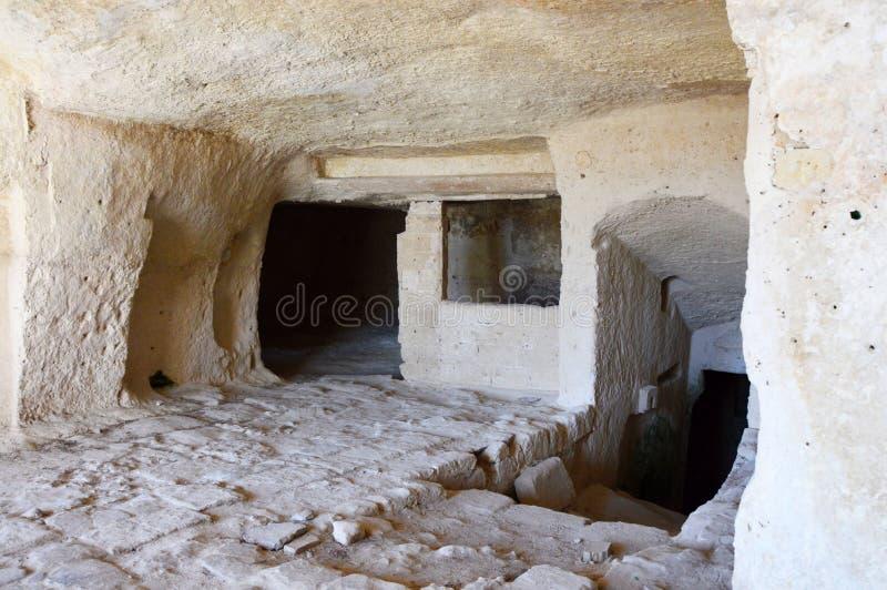 Inre av en grotta i forntida stad av Matera Matera stenar Sassi di Matera är en av de första mänskliga bosättningarna i Italien arkivbild