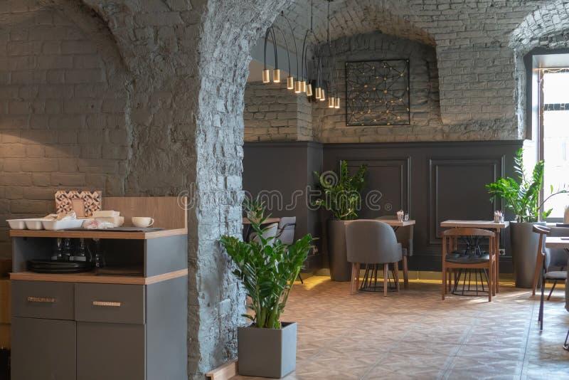 Inre av en hemtrevlig restaurang i vindstilen Stilfullt kafé med en grå vägg för tegelsten arkivbilder