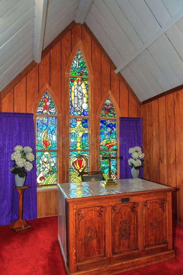 Inre av en liten kyrka, med altare- och målat glassfönster royaltyfria foton