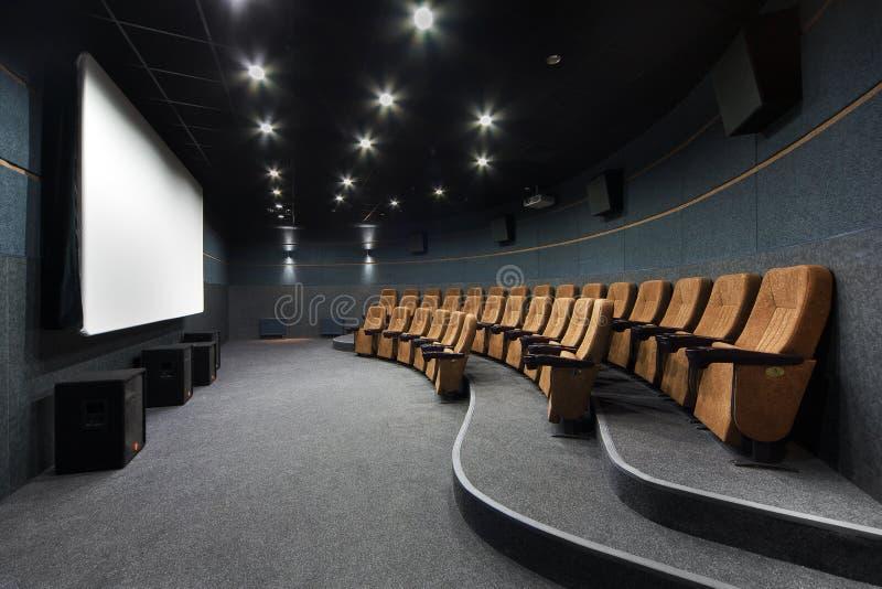 Inre av en liten teater med den apelsinstolar och skärmen arkivfoton