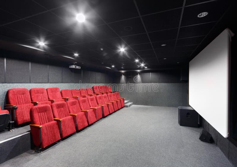 Inre av en liten teater med röda stolar och skärmen arkivbild