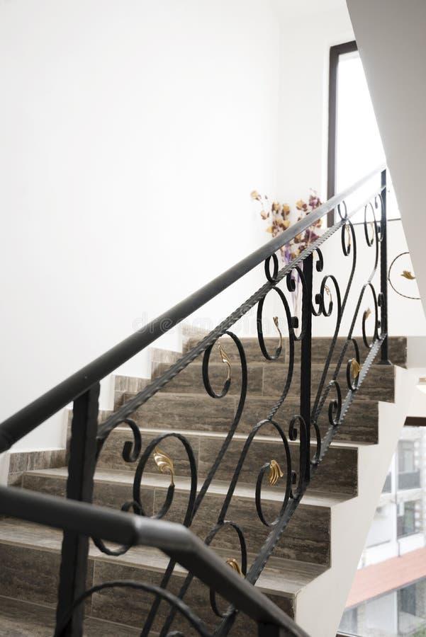 Inre av en lyxig fransk herrgård och en guld- trapparäcke En smidesjärntrappuppgång royaltyfri fotografi
