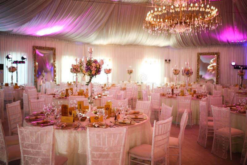 Inre av en lyxig vit brölloptältgarnering som är klar för gäster royaltyfria foton