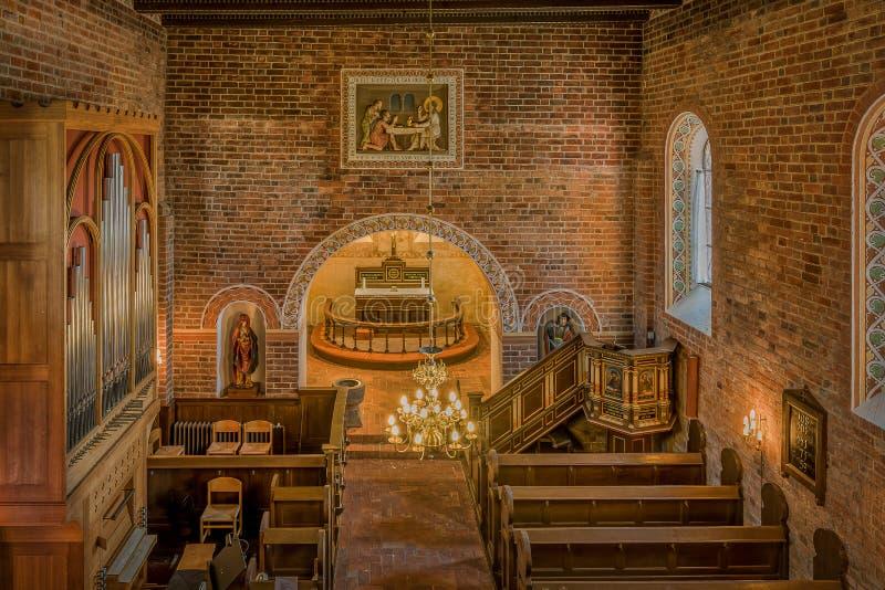 Inre av en medeltida dansk tegelstenkyrka royaltyfri bild