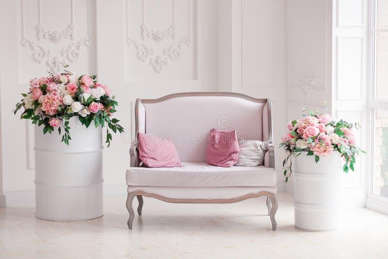 Inre av en snövit vardagsrum med en tappningsoffa och blommor royaltyfri bild
