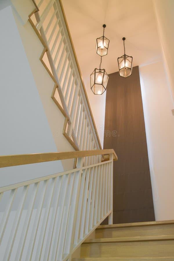 Inre av ett modernt hus med en trappuppgång och lampan i varm ton arkivfoton