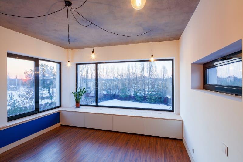Inre av ett tomt rum med laminaten och utsidaledningsnät arkivbild