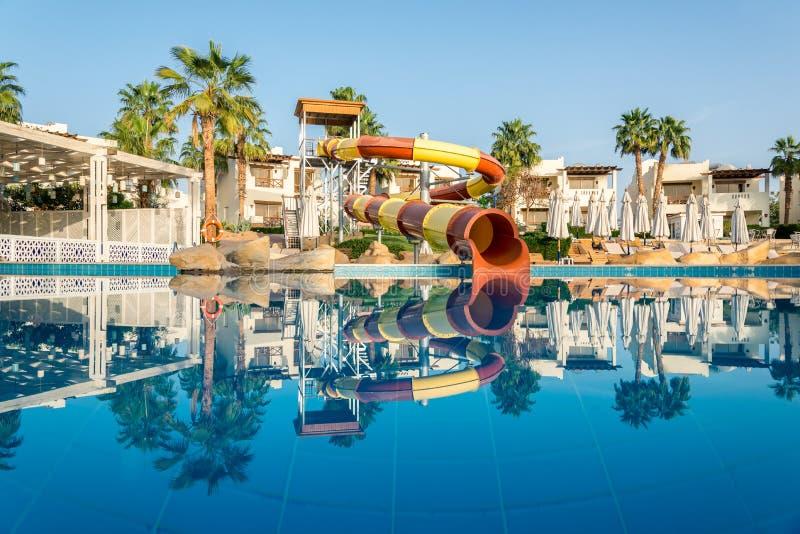 Inre av hotellet för rekreation Simbassängen med blått vatten, palmträd, solsängar och vatten parkerar röret arkivbilder