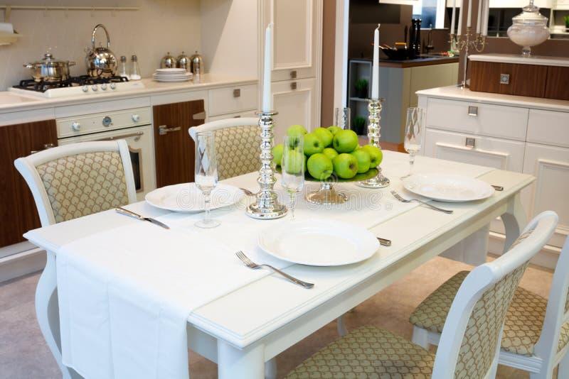 Inre av klassiskt vitt kök- och äta middagområde; tjänad som tabell för 4 personer; frukt; äpplen; vitstearinljus royaltyfri foto