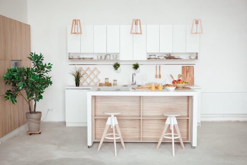Inre av litet vitt kök med ny frukt, två exponeringsglas av orange fruktsaft, bagett, röd kaviar, giffel och royaltyfri fotografi