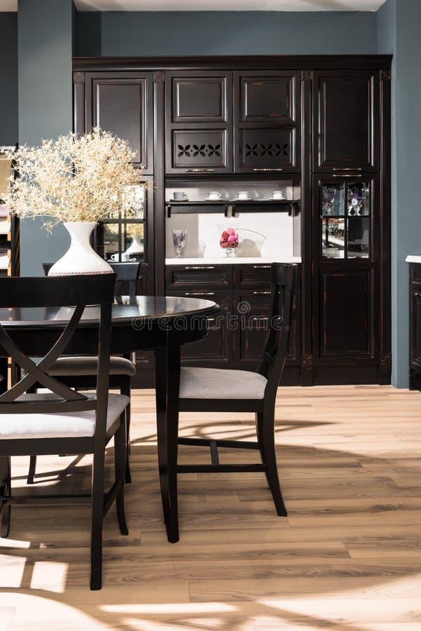 inre av modern matsal med den svarta möblemangvasen av torkade blommor på tabellen arkivfoto
