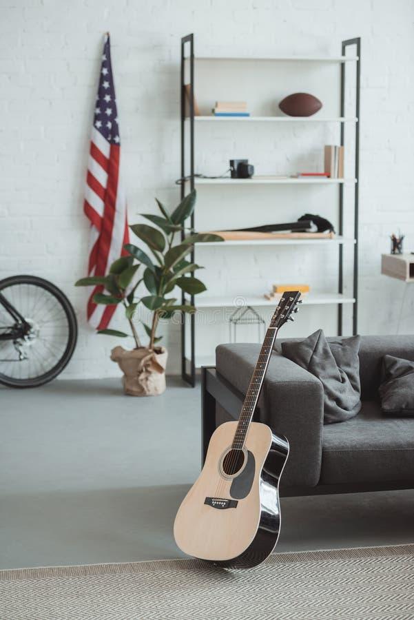 inre av modern vardagsrum med amerikanska flaggan, hyllor, lade in växten, gitarren och fåtöljen arkivfoton