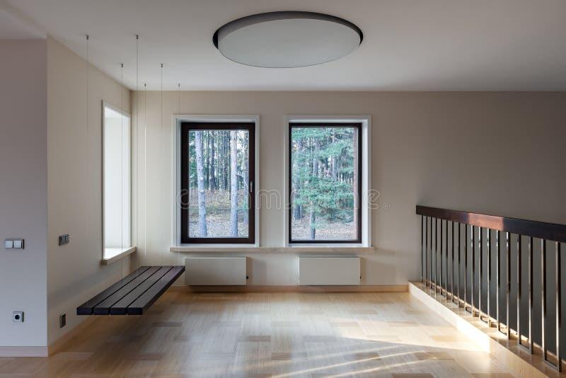 Inre av modernt tomt utrymme med den inställda bänken och fönster fotografering för bildbyråer