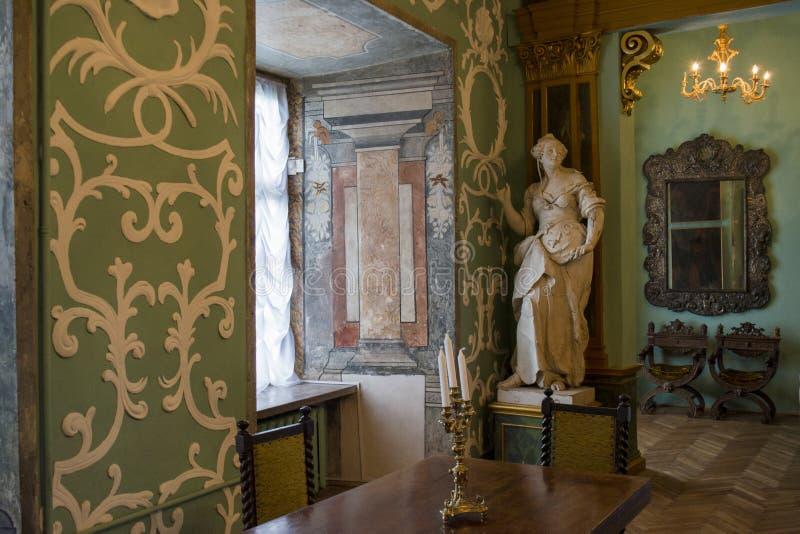 Inre av rummet med tabellen, stolar, staty i den forntida gamla slotten arkivfoton