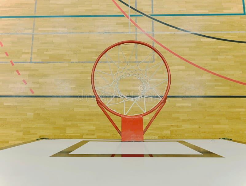 Inre av skolaidrottshallen med den basketbrädet och korgen Säkerhetsnät över fönster royaltyfri bild