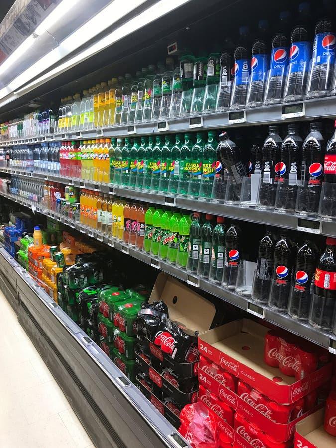 Inre av supermarketservicebutiken fyllde med gods på hyllor arkivbild