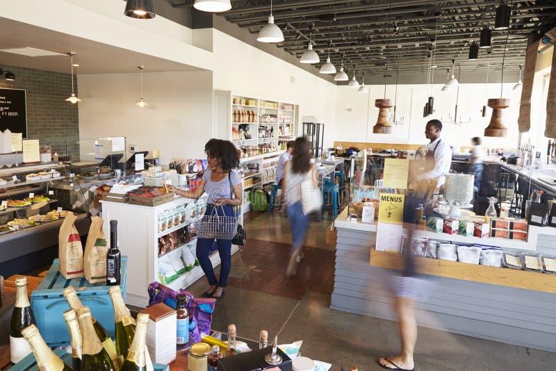 Inre av upptagen matvaruaffär med kunder arkivbild