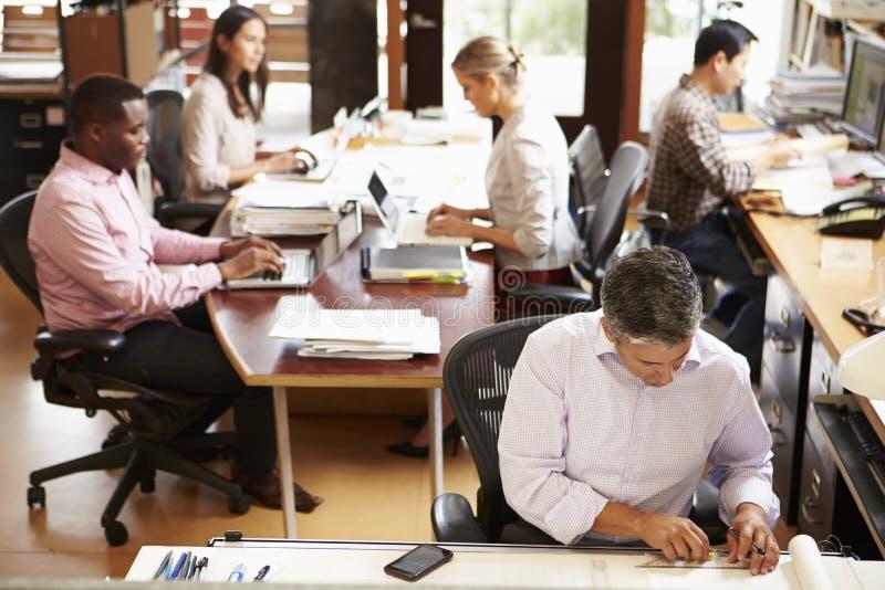Inre av upptagna arkitekts kontor med personalarbete royaltyfria bilder