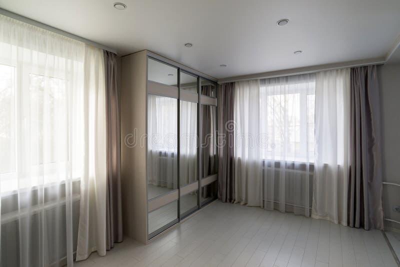 inre av vardagsrum med fönster- och spegelgarderoben arkivbilder