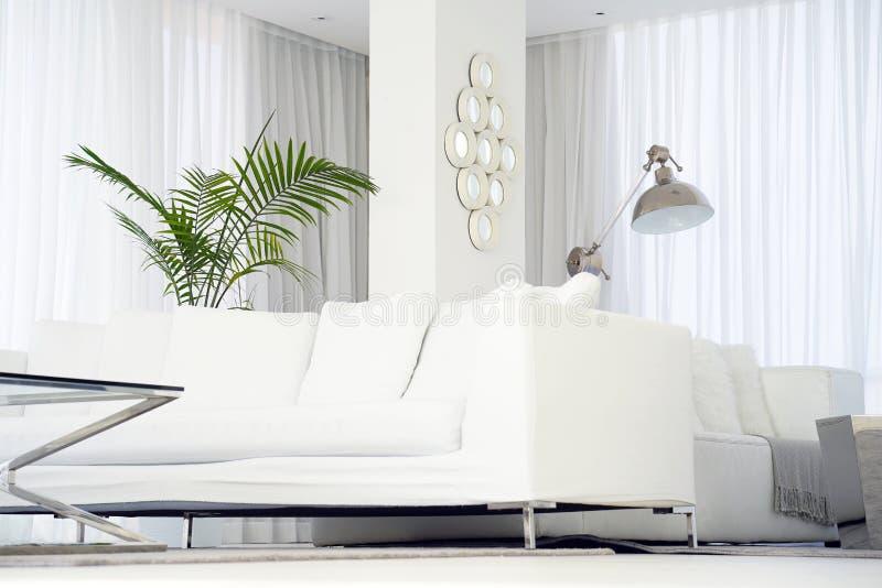 Inre av vardagsrummet av hotellet Härlig vardagsrum med den vita soffan Vit begreppsvardagsruminre modernt underlag arkivfoto