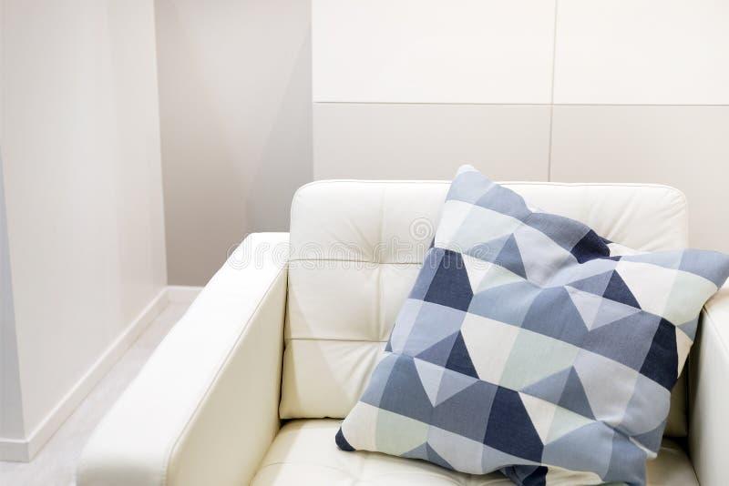 Inre av vardagsrummet med den vita soffan med färgrika kuddar och en filt royaltyfria bilder