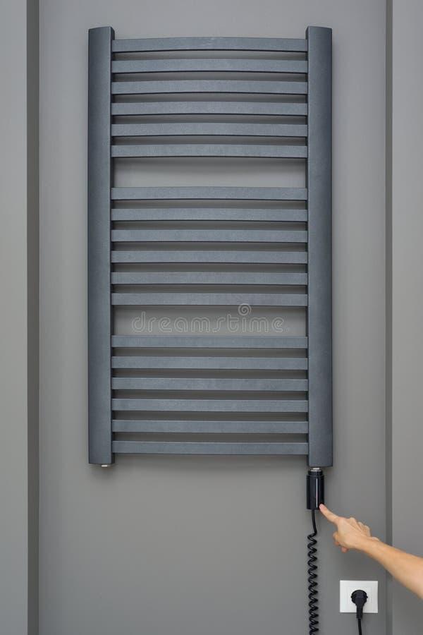 Inre beståndsdelar för närbild av badrummet, handdukelement Grå elektrisk thermostatic upphettad handdukstång handen för kvinna`  arkivbild