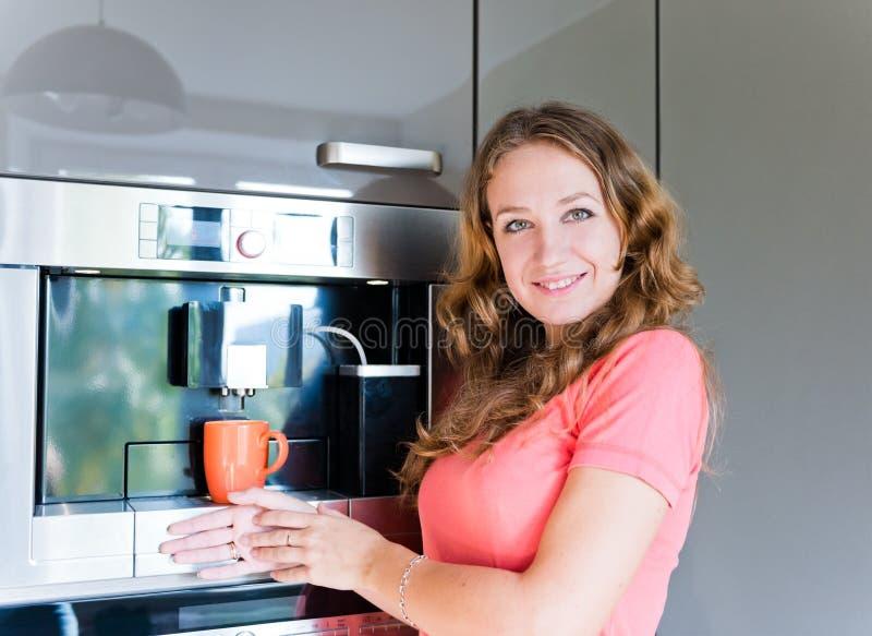 Inre för kök för maskin för kopp för kvinnadanandekaffe royaltyfria bilder
