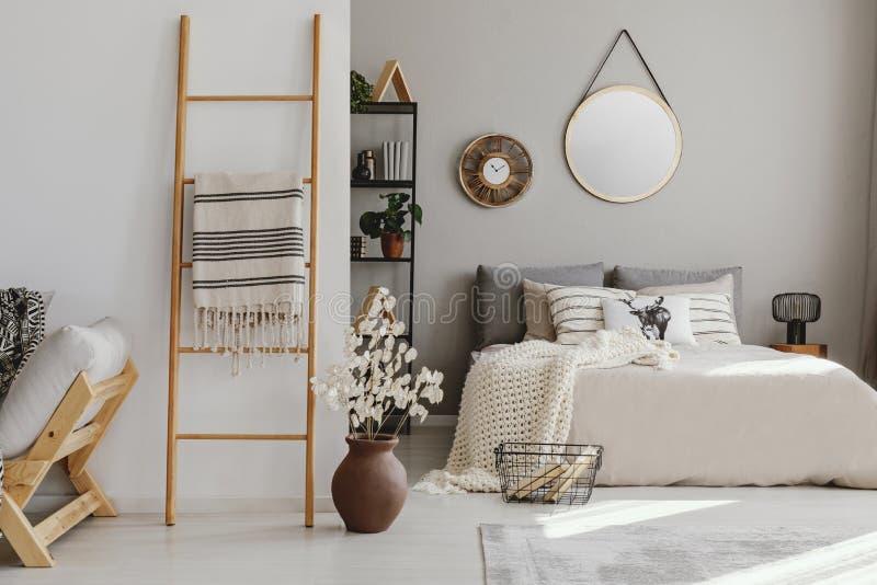 Inre för Scandi öppet utrymmesovrum med säng med rät maskafilten och många kuddar, kugge med böcker och dekor, matta på arkivfoton