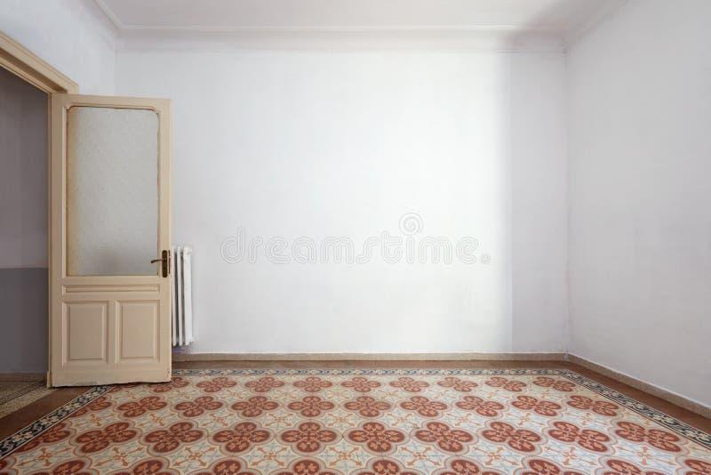 Inre för tomt vitt rum, belagt med tegel golv med blom- garnering arkivfoto