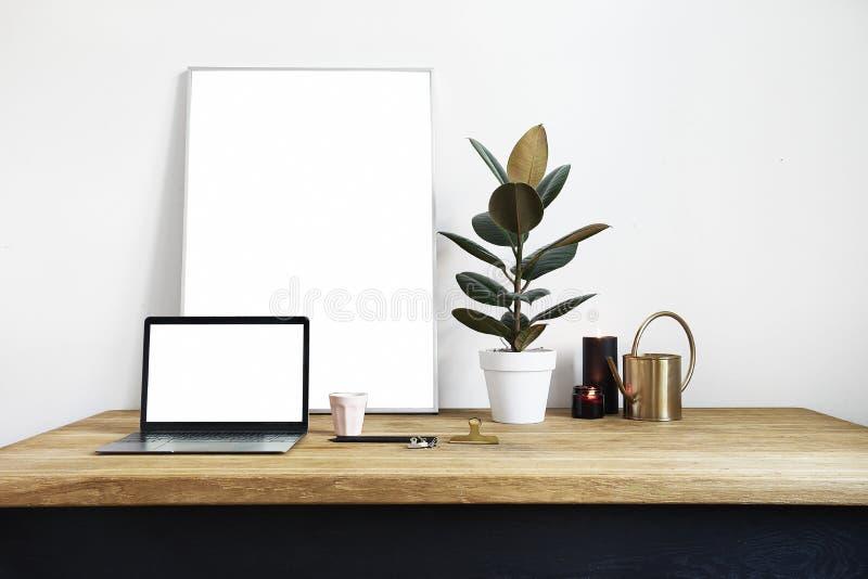 Inre för vitt rum med gröna växter på den lantliga trätabellen, modern personlig bärbar dator, affisch i ram med utrymme för orie fotografering för bildbyråer