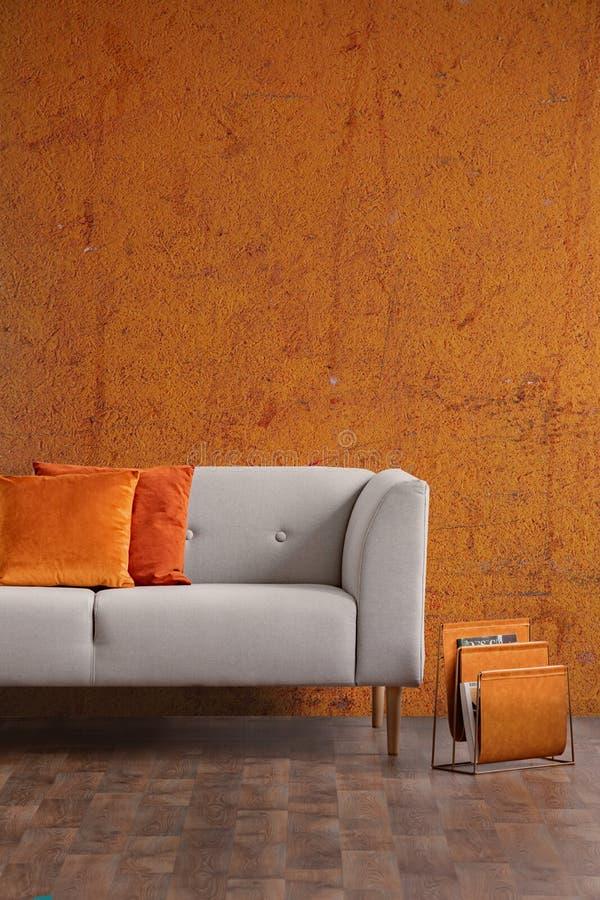 Inre för Wabi sabivardagsrum med den gamla orange väggen och den nya stilfulla soffan, verkligt foto med kopieringsutrymme arkivbilder