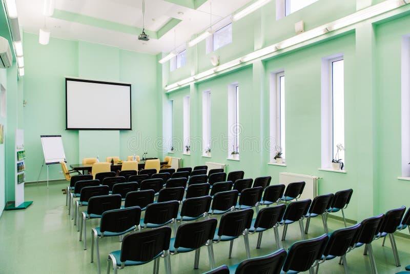 Inre konferenskorridor med massor av stolar och ett flipdiagram royaltyfria foton