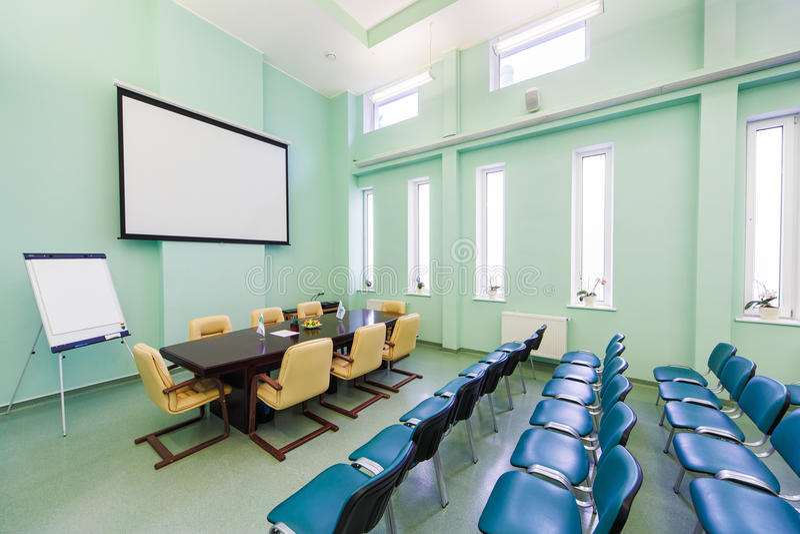Inre konferenskorridor med massor av stolar och ett flipdiagram fotografering för bildbyråer