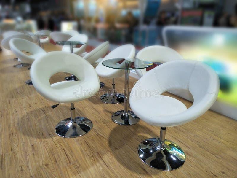 Inre med design och dekorativa, lyxiga och moderna glass tabeller och vitstolar i restaurang royaltyfri bild